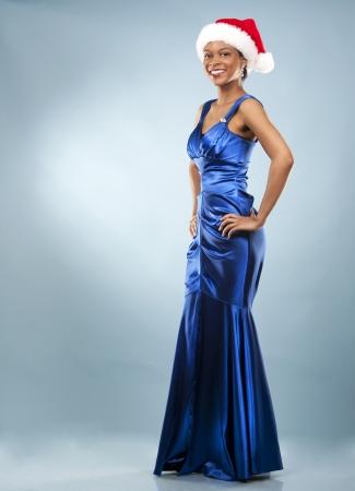 beautiful woman wearing blue evening dress and Christmas hat Stock Photo - 22736407