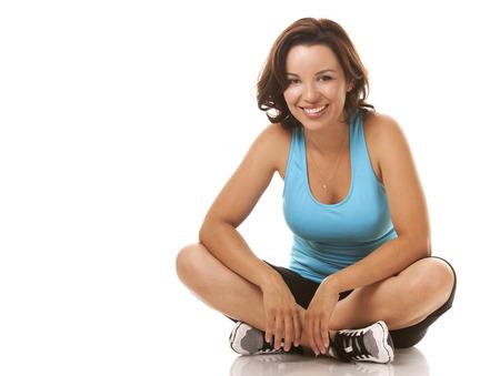 sitting down: brunette caucasian fitness model  sitting down on white background Stock Photo