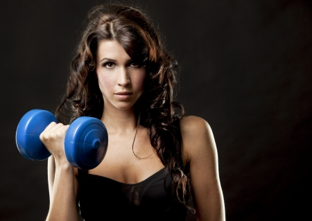 heavy weight: fitness model brunette holding weights on black background