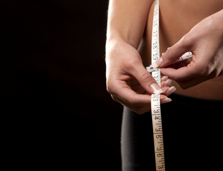 fitness model is measuring her waist on black background Stock Photo