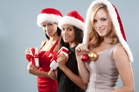 beautiful three women wearing christmas hats on blue background photo