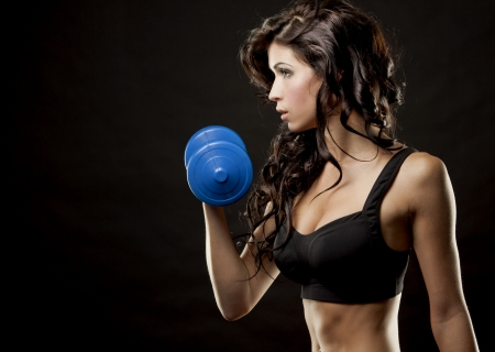 fitness model brunette holding weights on black background