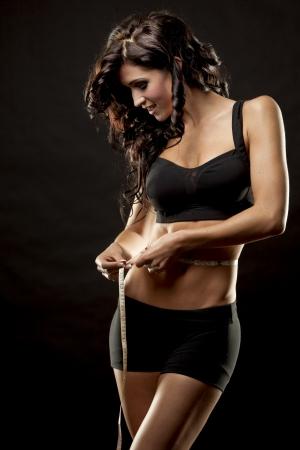 fitness model is measuring her waist on black background Stockfoto
