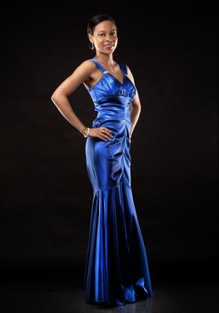 beautiful woman wearing blue evening dress on black background photo