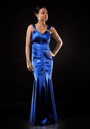 traje de gala: hermosa mujer con un vestido de noche azul sobre fondo negro Foto de archivo