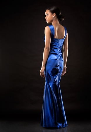beautiful woman wearing blue evening dress on black background photo
