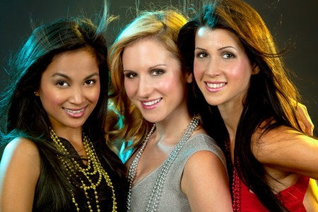 beautiful three women having fun during party on dark background photo