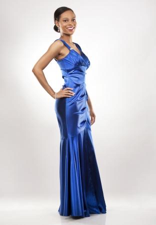 beautiful woman wearing blue evening dress on light background photo
