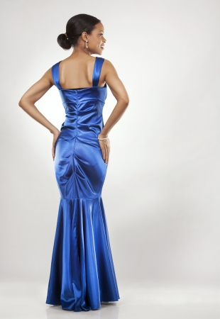 beautiful woman wearing blue evening dress on light background photo