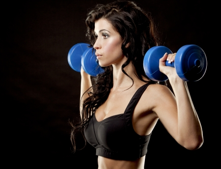 fitness model brunette holding weights on black background Stock Photo - 23694277