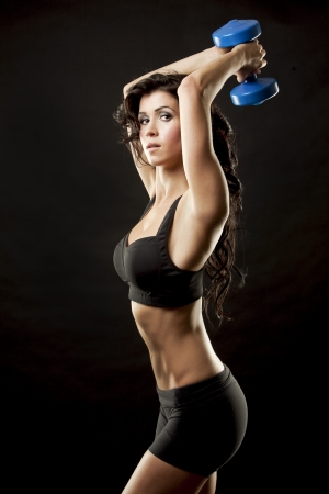 heavy lifting: fitness model brunette holding weights on black background