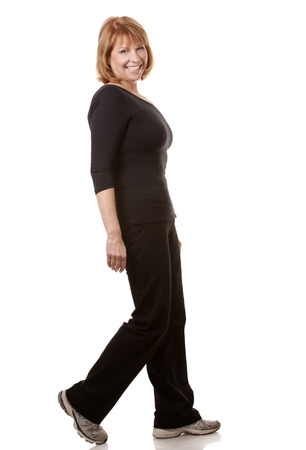 mature woman is wearing black workout outfit on white background Stock Photo
