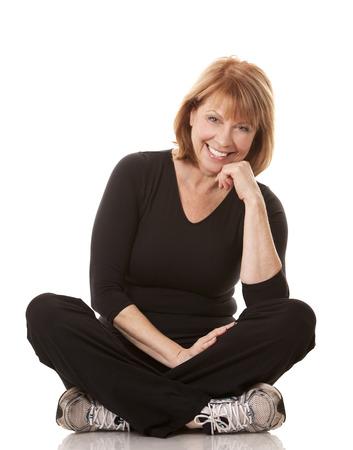 rijpe vrouw draagt een zwarte workout outfit op witte achtergrond Stockfoto