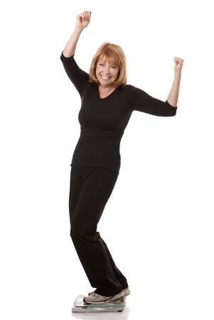 rijpe vrouw staat op gewicht schaal witte achtergrond Stockfoto