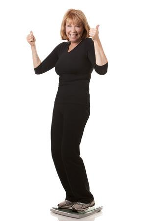 Reife Frau ist auf die Waage weißem Hintergrund stehend Standard-Bild - 24108811