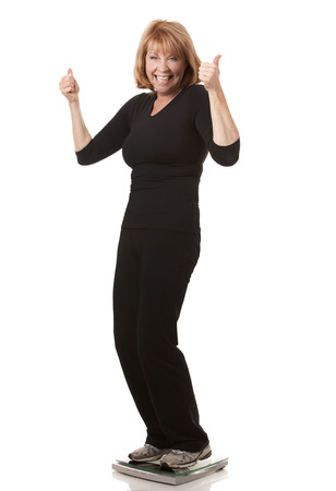 mature woman is standing on weight scale white background