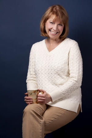 mature brunette: mature casual woman holding cup of tea on dark blue background