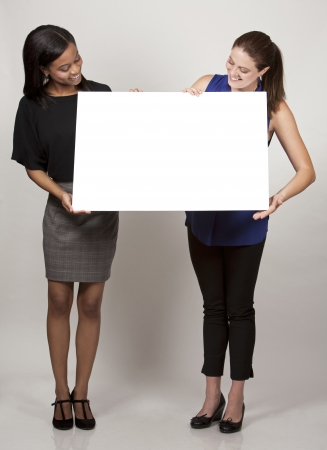 two women holding white board on light grey background photo