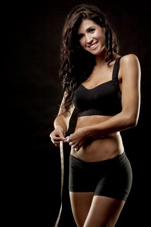 woman black background: fitness model brunette measuring waist on black background
