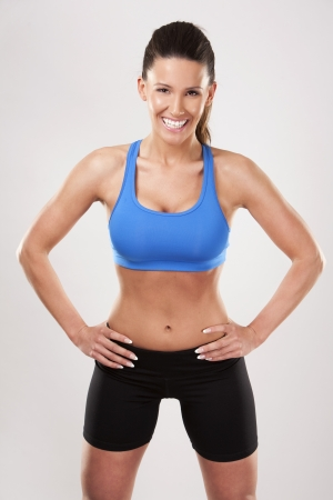 fitness model brunette wearing blue outfit on light background Stock Photo - 25068472