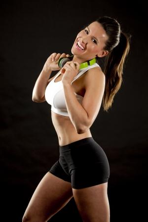 woman black background: fitness model brunette wearing headset on black background