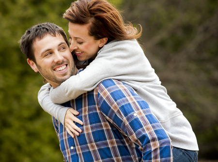 piggy back: young couple wearing casual outfits in the park