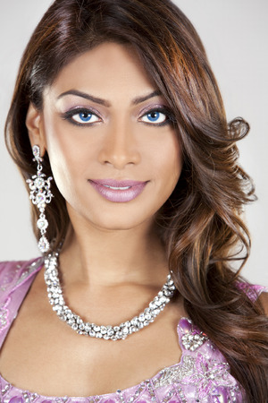 costume jewelry: beautiful woman wearing indian traditional outfit on light background