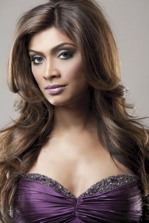 beautiful woman wearing purple dress on grey  background photo