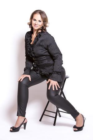 beautiful woman wearing black upscale outfit on white background 免版税图像