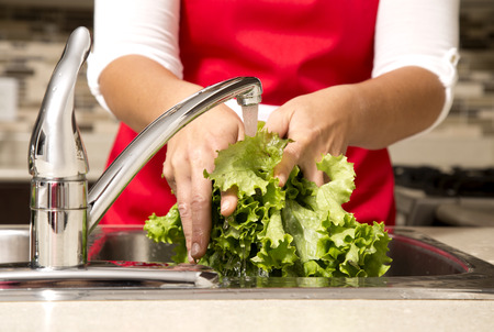 ingredients tap: woman washing vegetables in the sink home kitchen