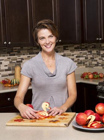 caucasian woman preparing apple thanksigiving decorations in the kitchen photo