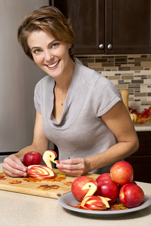 caucasian woman preparing apple thanksigiving decorations in the kitchen