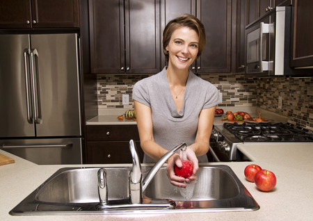water sink: woman washing apples in the sink home kitchen