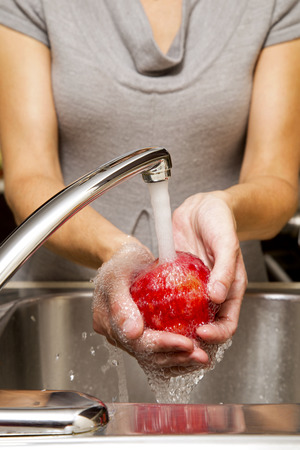 ingredients tap: woman washing apples in the sink home kitchen