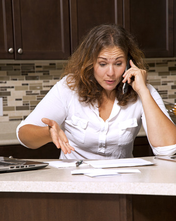 stressed woman looking at bills while sitting in the kitchen photo