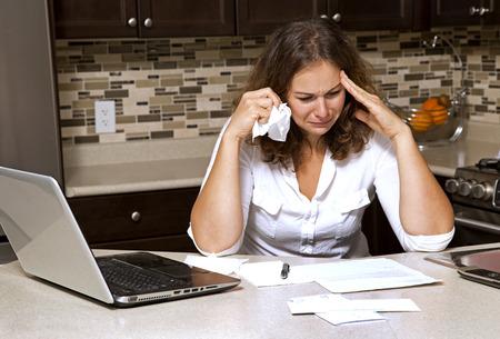 부엌에 앉아있는 동안 청구서를 보면서 스트레스를받은 여자 스톡 콘텐츠