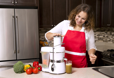 woman making juice from raw vegetables in the kitchen photo