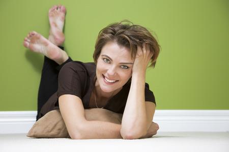 caucasian woman lying down on beige carpet in green room