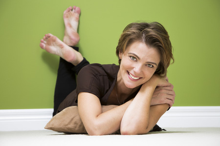 carpet and flooring: caucasian woman lying down on beige carpet in green room