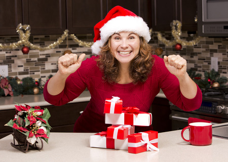 christmas tea: excited woman wearing Christmas hat in the kitchen surrounded by presents