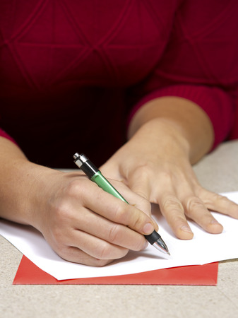 person writing: happy woman wearing Christmas hat in the kitchen writing a card