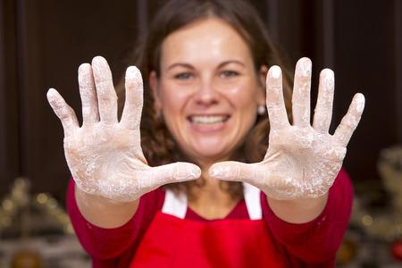 manos sucias: Mujer que muestra las manos sucias con harina mientras hornear en la cocina