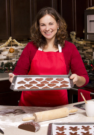 wood cutter: woman making ginger bread cookies in the kitchen Stock Photo