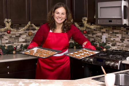 galletas de jengibre: Mujer que hace las galletas de pan de jengibre en la cocina Foto de archivo