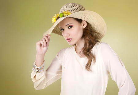 light green background: woman wearing hat with flowers on light green background