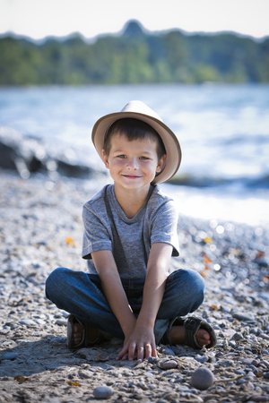 cuacasian boy smiling wearing a hat on the beach