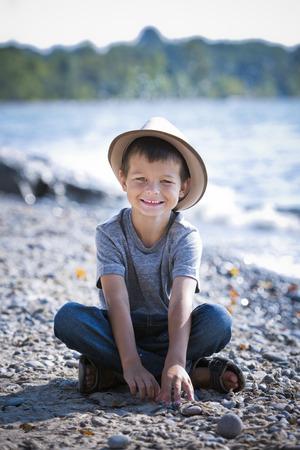 niños sentados: sonriente con un sombrero en la playa niño caucásica