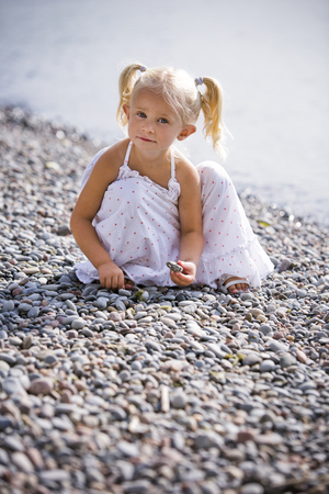 kids outside: caucasian girl smiling and playing on the beach