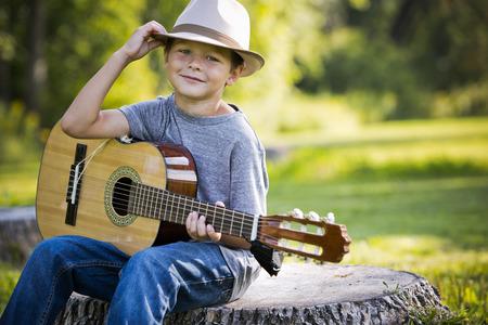 Cuacasian garçon avec sa guitare dans le parc extérieur Banque d'images - 48180487
