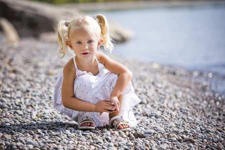 child portrait: caucasian girl smiling and playing on the beach